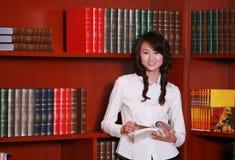 Lettura della giovane donna nella libreria Fotografie Stock Libere da Diritti