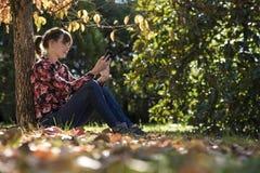 Lettura della giovane donna qualcosa su un dispositivo digitale Fotografia Stock