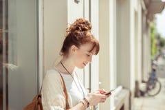 Lettura della giovane donna sms sul suo cellulare Fotografia Stock
