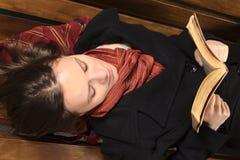 Lettura della giovane donna sul banco Immagini Stock