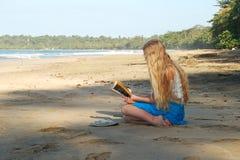 Lettura della giovane donna sulla spiaggia Fotografia Stock