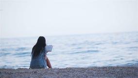 Lettura della giovane donna sulla spiaggia bianca tropicale video d archivio