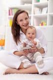 Lettura della neonata il suo primo libro con la madre Fotografia Stock