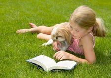 Lettura della ragazza con il cane all'aperto Fotografia Stock Libera da Diritti