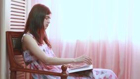 lettura della ragazza del libro una donna in una sedia dalla finestra stock footage