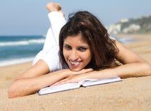 Lettura della ragazza sulla spiaggia Fotografie Stock