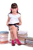 Lettura della scolara che si siede sul mucchio dei libri Immagini Stock