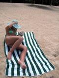 Lettura della signora sulla spiaggia sabbiosa Fotografia Stock