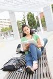Lettura della studentessa sulla città universitaria del banco Fotografia Stock Libera da Diritti