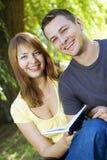 Lettura delle coppie all'aperto Fotografia Stock Libera da Diritti