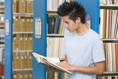 Lettura dello studente universitario nella libreria Immagine Stock