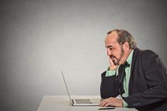 Lettura di lavoro dell'uomo qualcosa sul suo computer portatile Immagine Stock Libera da Diritti