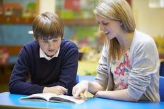 Lettura di With Male Pupil dell'insegnante allo scrittorio in aula Immagine Stock