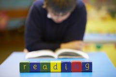 Lettura di parola compitata in blocchi di legno con l'allievo dietro Fotografia Stock