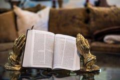 Lettura di sacra scrittura con le mani di preghiera Fotografie Stock Libere da Diritti