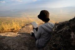 Lettura di seduta della donna ed osservare fuori la bella vista naturale fotografie stock libere da diritti