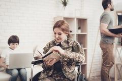 Lettura disabile del libro di Woman In Wheelchair del soldato fotografia stock libera da diritti