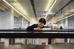 Lettura e scrittura della ragazza della scuola secondaria nella biblioteca Fotografia Stock Libera da Diritti