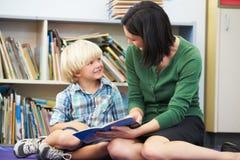 Lettura elementare dell'allievo con l'insegnante In Classroom Fotografie Stock