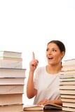 Lettura emozionante della donna dietro la tavola fra il mucchio due dei libri Fotografie Stock Libere da Diritti