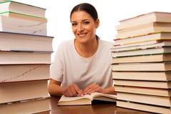 Lettura emozionante della donna dietro la tavola fra il mucchio due dei libri Immagini Stock Libere da Diritti