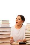 Lettura emozionante della donna dietro la tavola fra il mucchio due dei libri Fotografie Stock