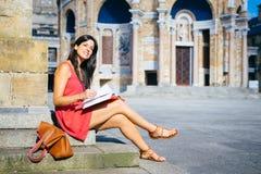 Lettura femminile dello studente di college all'università Fotografia Stock