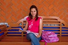 Lettura femminile dello studente di college sul banco lungo Fotografie Stock Libere da Diritti