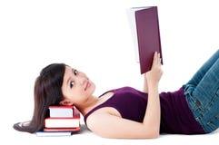 Lettura femminile sveglia con la testa che riposa sui libri Immagine Stock