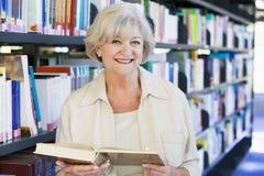 Lettura maggiore della donna in una libreria Immagine Stock
