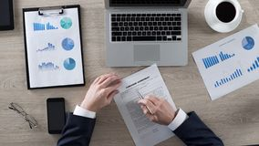 Lettura maschio ricca ed imparare accordo di acquisto in ufficio, affare, vista superiore fotografie stock