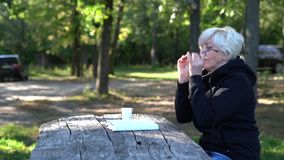 Lettura matura attraente della donna in un parco video d archivio