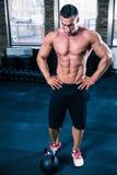 Lettura muscolare dell'uomo per l'allenamento con la palla del bollitore Immagini Stock