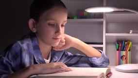Lettura nella notte, ragazza che studia nello scuro, bambino che impara, compito del bambino della scuola stock footage
