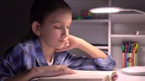 Lettura nella notte, ragazza che studia nello scuro, bambino che impara, compito del bambino della scuola archivi video