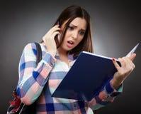 Lettura preoccupata dello studente da un taccuino e parlare con telefono Immagine Stock Libera da Diritti