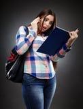 Lettura preoccupata dello studente da un taccuino e parlare con telefono Fotografie Stock Libere da Diritti