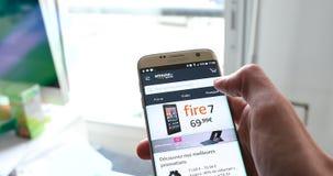 Lettura rapida del deposito online di acquisto di Amazon sul suo smartphone moderno stock footage