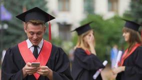 Lettura rapida laureata sullo smartphone vicino all'accademia, amici che chiacchierano sul fondo archivi video