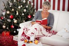 Lettura senior di signora davanti all'albero di Natale Immagine Stock