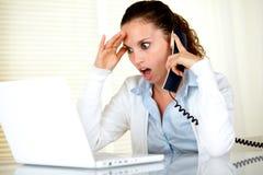 Lettura sorpresa della giovane donna sullo schermo del computer portatile Fotografia Stock