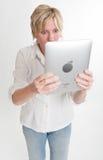 Lettura stupita della donna da un ridurre in pani del PC Fotografia Stock Libera da Diritti