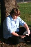Lettura teenager del ragazzo nella sosta fotografia stock