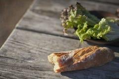 Letuce e pane sulla tavola di legno Fuoco selettivo Fotografie Stock Libere da Diritti