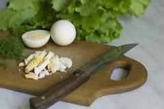Letusse und Eier des grünen Salats auf hackendem Brett Lizenzfreies Stockbild