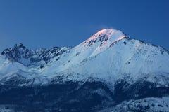 Letzte rosa Lichter auf dem weißen geschneiten Gipfel Lizenzfreies Stockbild