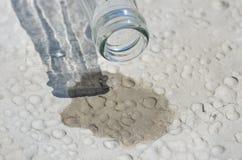 Letzte Wassertropfen von einer Flasche in der Wüste Stockbild