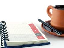 Letzter Tag von Dezember und erster Tag von Januar auf Kalendertagebuchseite mit Kaffeetasse auf weißem Hintergrund Stockfotos