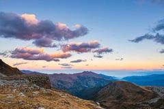 Letztes warmes Sonnenlicht auf alpinem Tal mit glühenden Bergspitzen und szenischen Wolken Italienische französische Alpen, Somme Stockfotos