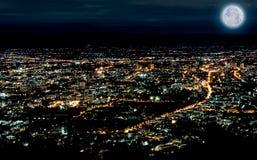 Leuchten der Stadt in der Nachtzeitszene mit blauem Mond Lizenzfreie Stockfotos